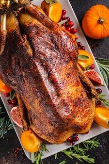 Рождество запеченная утка с травами и фруктами на серой тарелке на белом фоне