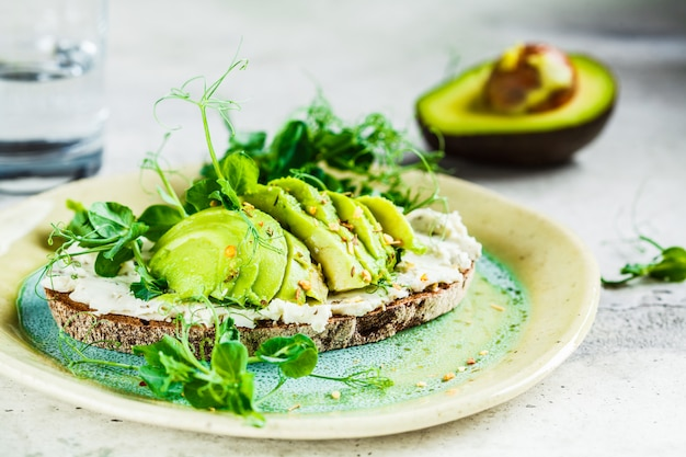 Тост из ржаного хлеба со сливочным сыром и авокадо на красивой тарелке