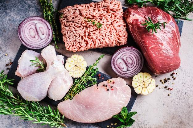Концепция диета плотоядных животных. сырое мясо курицы, говядины, фарша и индейки на темном фоне, вид сверху, плоское положение.