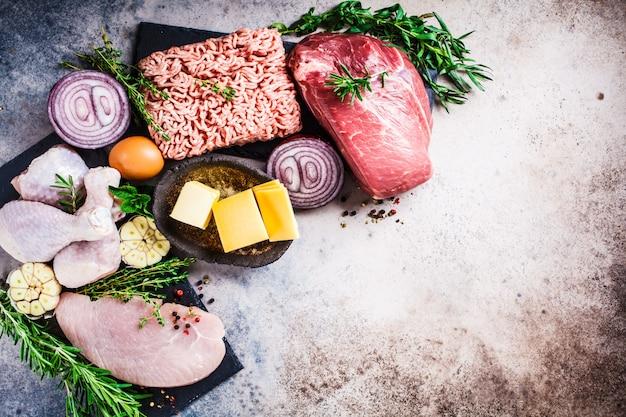 肉食ダイエットのコンセプト。鶏肉、牛肉、バター、チーズ、卵、ひき肉、暗い背景に七面鳥の生肉、コピースペース、平面図、フラットレイアウト。
