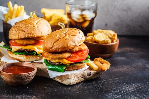 Чизбургеры, картофель фри, начос, пончики, сода и самородки
