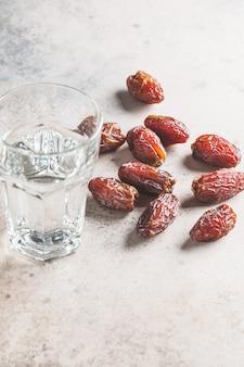 日付とコップ一杯の水、コピースペース。イフタール食品のコンセプト。
