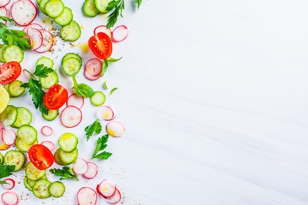 Концепция здорового питания. куски томата, редиски и огурца на белой предпосылке, взгляд сверху, космосе экземпляра.