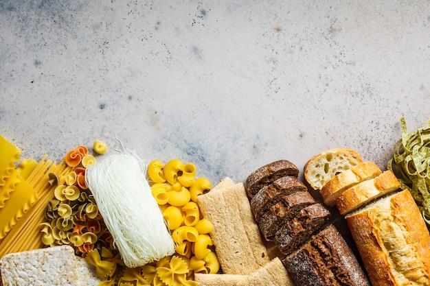 Различные макароны фон. хлеб и разные макаронные изделия на серо-голубой предпосылке, космосе экземпляра, взгляд сверху.