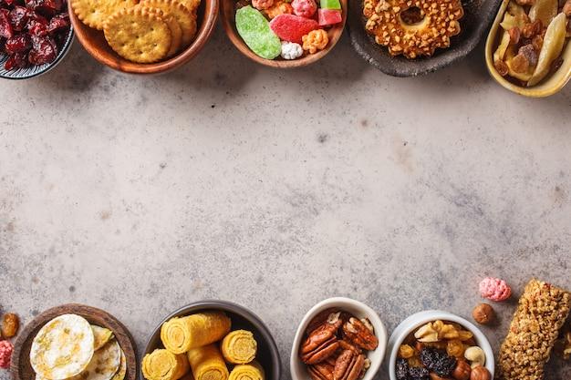 さまざまなスナックや灰色の背景にお菓子。ワッフル、ナッツ、お菓子、クッキー、チップス、フルーツ、トップビュー。