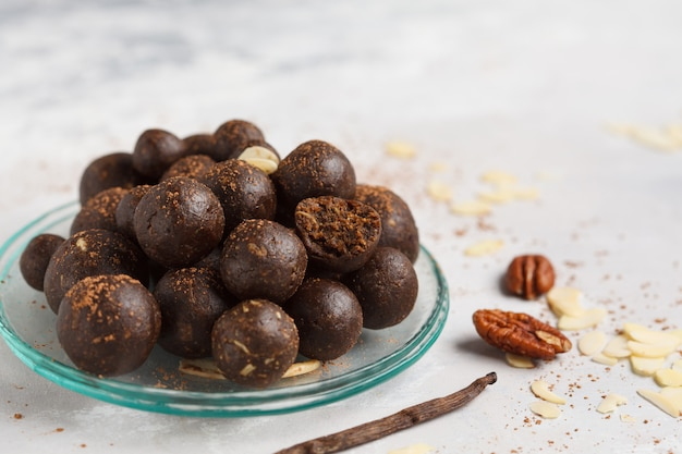 ナッツ、ナツメヤシ、ココアとバニラチョコレート生ビーガンスイートボール。健康的なビーガンフードコンセプト。灰色の背景