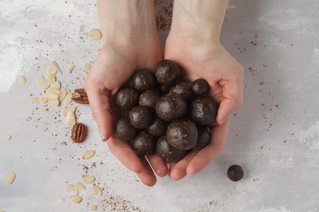 Ванильно-шоколадные сырые веганские сладкие шарики с орехами, финиками и какао в руках. концепция здорового веганского питания. серый фон