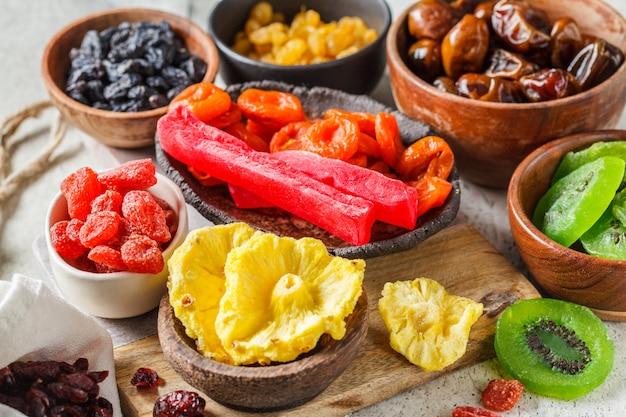 Разнообразие сухофруктов в мисках. финики, изюм, курага и экзотические сушеные ананасы, папайя и киви, серый фон.
