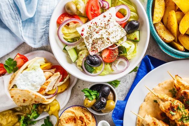 Греческая еда: греческий салат, куриные сувлаки, гироскопы и запеченные картофельные дольки на сером фоне, вид сверху. концепция традиционной греческой кухни.