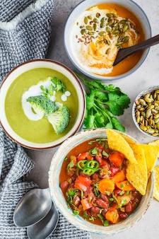 Набор веганских супов. мексиканский фасолевый суп, суп из брокколи и суп из пюре из тыквы, вид сверху.