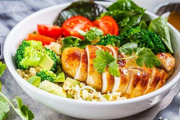 Концепция сбалансированного питания. салат из курицы, брокколи и квиноа в белый шар, серый фон.