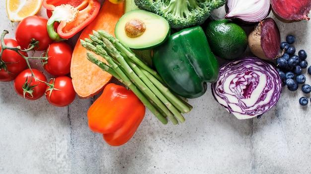 虹色の野菜と果実の背景、トップビュー。デトックス、ビーガンフード、ジュースやサラダの材料。