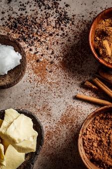 チョコレートの背景を作るための材料。暗い背景、上面にココア、ココアバター、砂糖、シナモン、ココナッツオイル。