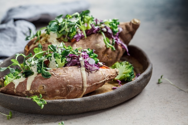 キノア、ブロッコリー、キャベツ、暗い背景を詰めた焼き芋。