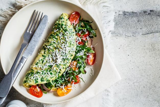緑のほうれん草のオムレツ、チーズ、ルッコラ、トマトの白いプレート、上面図。