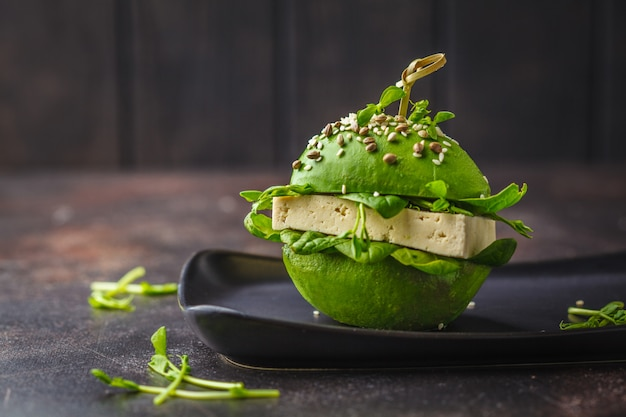 黒い皿にビーガンアボカド豆腐バーガー。健康的なデトックス食品、植物ベースの食品のコンセプト。