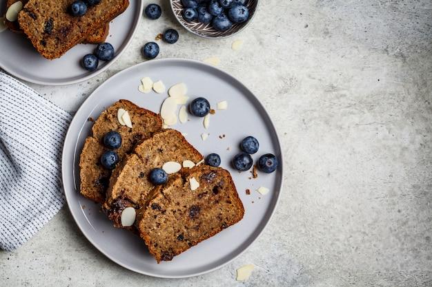 Куски бананового хлеба с ягодами на серой плите, взгляд сверху. концепция здорового веганского питания.