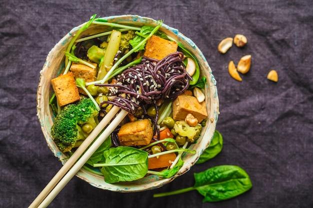 アジアのビーガン炒め豆腐、米麺、野菜、暗い背景。