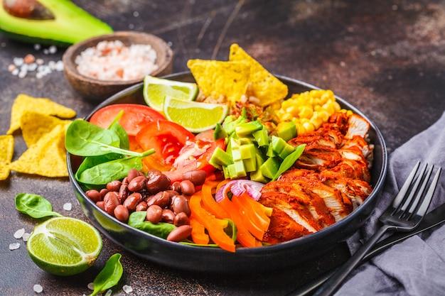 米、豆、トマト、アボカド、コーン、ほうれん草のメキシコ風チキンブリトーボウル。メキシコ料理料理のコンセプトです。