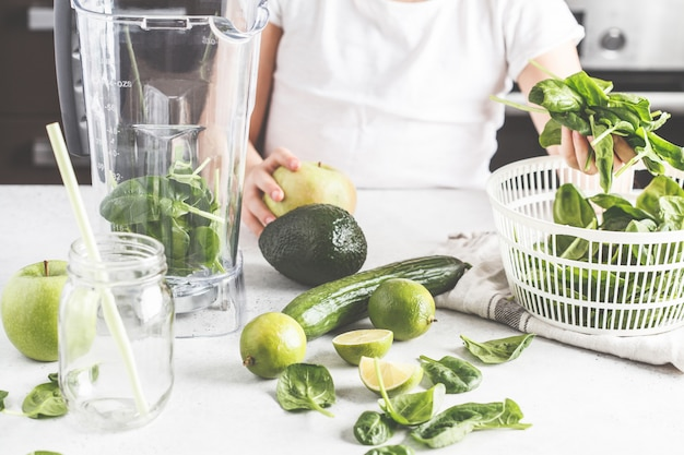 ほうれん草アップルキュウリのスムージーを調理する子供。健康的な植物ベースの食品のコンセプト。