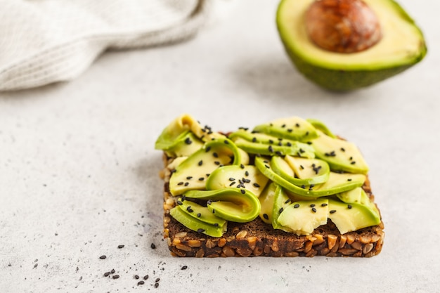 Авокадо тост на здоровый кунжутный хлеб с кунжутом, вид сверху. концепция здорового веганского питания.
