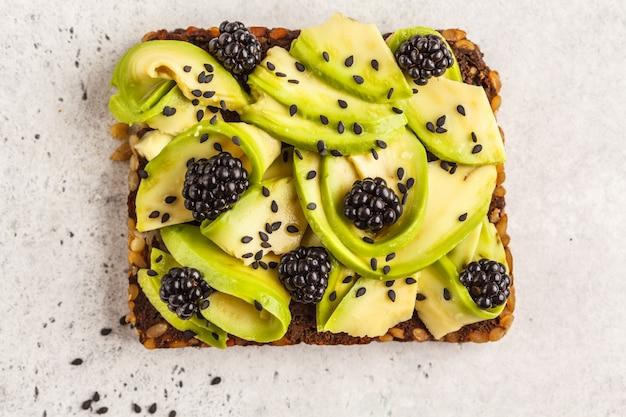 Авокадо тост на здоровый кунжутный хлеб с ежевикой и кунжутом, вид сверху. концепция здорового веганского питания.