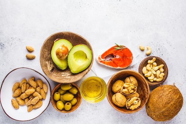 健康的な脂肪食品の背景。魚、ナッツ、オイル、オリーブ、アボカド、白背景、上面図
