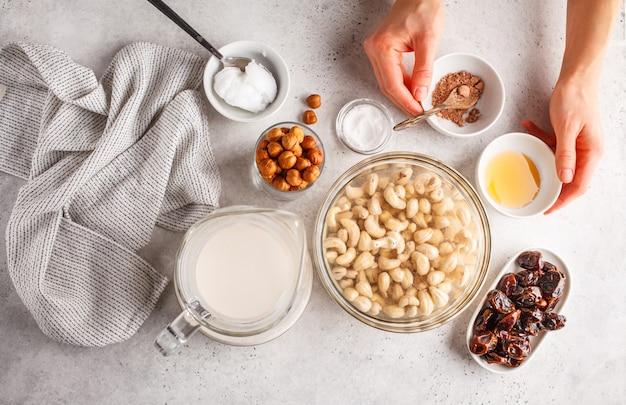 Ингридиенты для сырцового торта вегана, торта кешью на белой предпосылке.