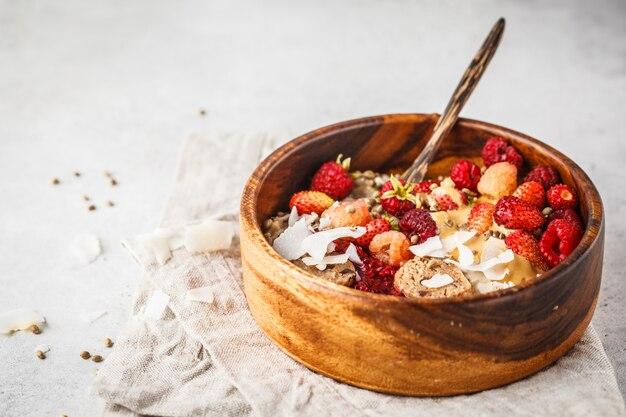 果実、生ビーガンボールとピーナッツバター、コピースペースとオートミールのお粥のトレンディなビーガンボウル。