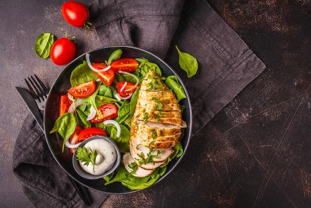 ほうれん草、トマト、シーザードレッシング、暗い背景と焼き鶏の胸肉サラダ。