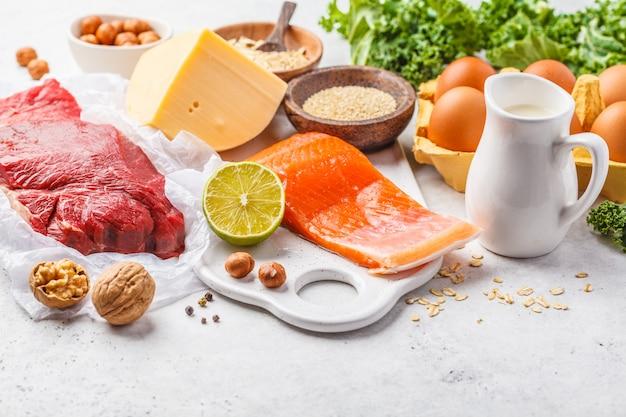 バランスの取れたダイエット食品の背景。タンパク質食品:魚、肉、チーズ、キノア、白い背景の上のナッツ。