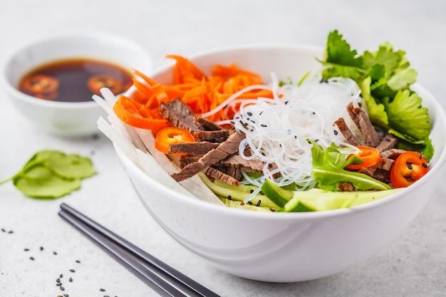 パンチャラのサラダボール。白いボウルに牛肉と唐辛子野菜のサラダとベトナムのライスヌードル