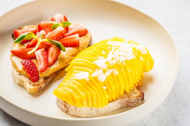 白い皿にマンゴー、イチゴ、ピーナッツバターのビーガンフルーツサンドイッチ。