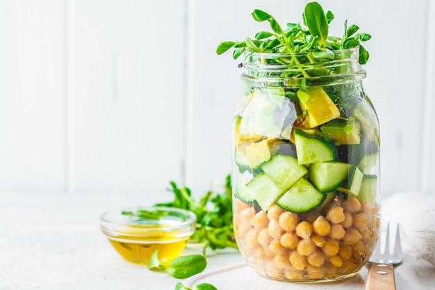 瓶、白い背景、コピー領域のひよこ豆とグリーンサラダ。