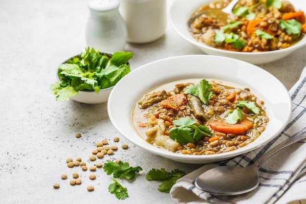 白いプレート、白い背景、垂直の野菜とレンズ豆のスープ。植物ベースの食品、清潔な食事。