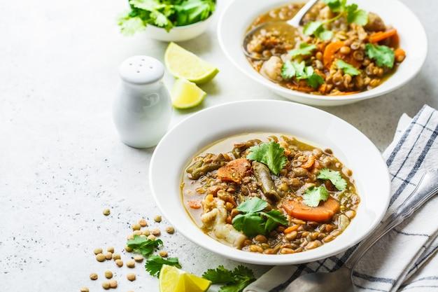 白いプレート、白い背景で野菜とレンズ豆のスープ。植物ベースの食品、清潔な食事。