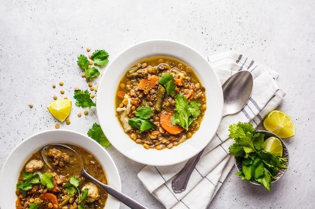 白い皿、白い背景、上面の野菜とレンズ豆のスープ。植物ベースの食品、清潔な食事。