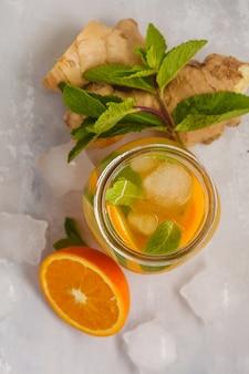 ガラスの瓶、白い背景、コピースペース、上面図のミントとジンジャーオレンジアイスティー。夏の爽やかなドリンクのコンセプトです。