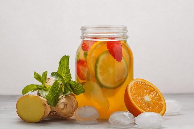 ガラスの瓶、白い背景、コピースペースにミントと生姜フルーティーなアイスティー。夏の爽やかなドリンクのコンセプトです。