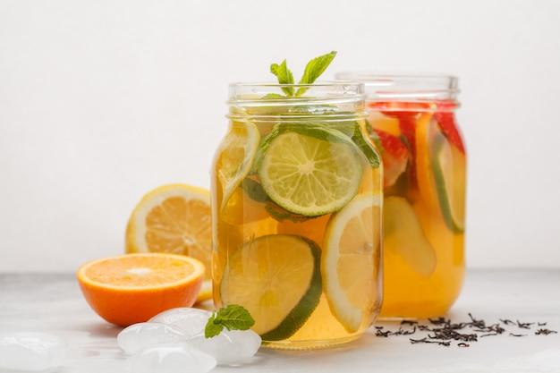 フルーツアイスティーとジンジャーハーブアイスティーのミント入りガラス瓶、白い背景、コピースペース。夏の爽やかなドリンクのコンセプトです。