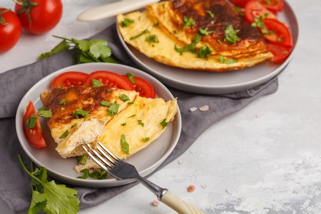 Вкусный яркий яичный омлет с сыром и овощами. концепция еды завтрака, белая предпосылка