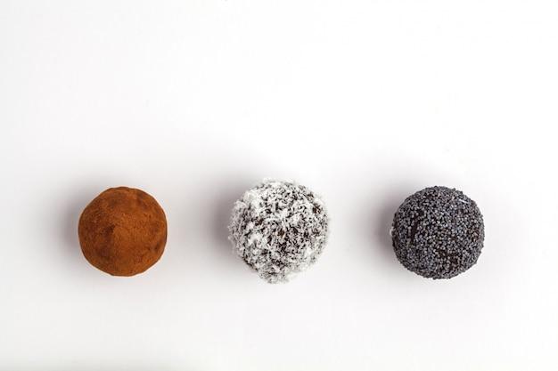 自家製の健康的なビーガン生エネルギーボール、キャロブ、ポピー、ココナッツ、白い背景で隔離のトップビュー