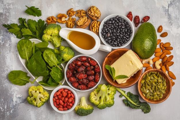 油、ナッツ、アボカド、バター、健康的な脂肪、ローズヒップ、パセリ、種子、ほうれん草。白い背景、上面図