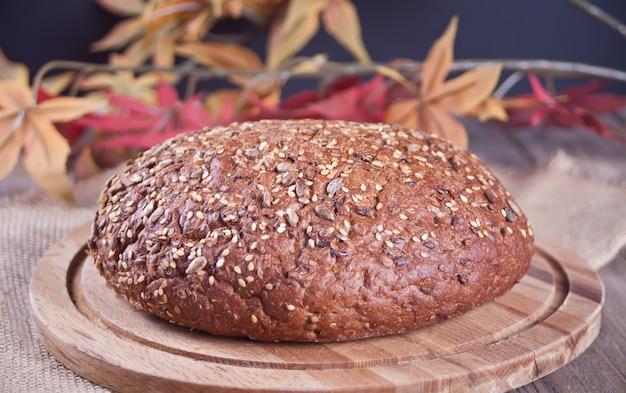 Свежеиспеченный хлеб на деревянном кухонном столе в осеннем стиле