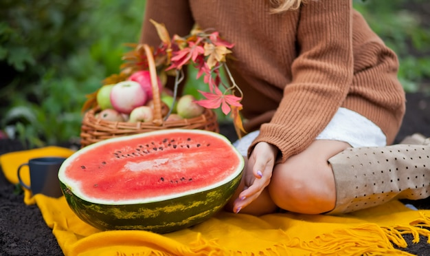 ピクニックで熟したスイカを持つ女性。