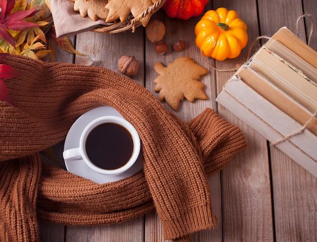 一杯のコーヒー、紅葉、カボチャ、クッキー、本、木製のテーブルの上のセーター。秋の収穫。秋のコンセプト。上面図。