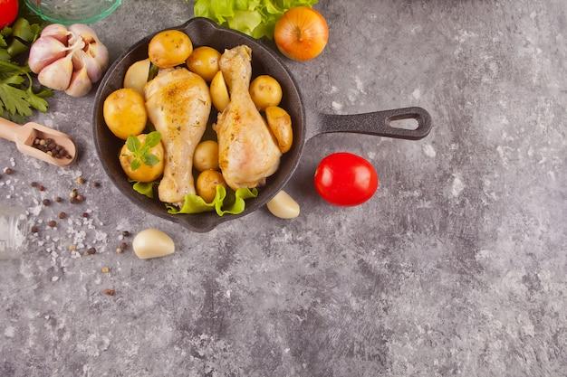 ローストチキンの脚に、ポテト、スパイス、ハーブを添えた黒い鍋に野菜を添えます。上面図。コピースペース。