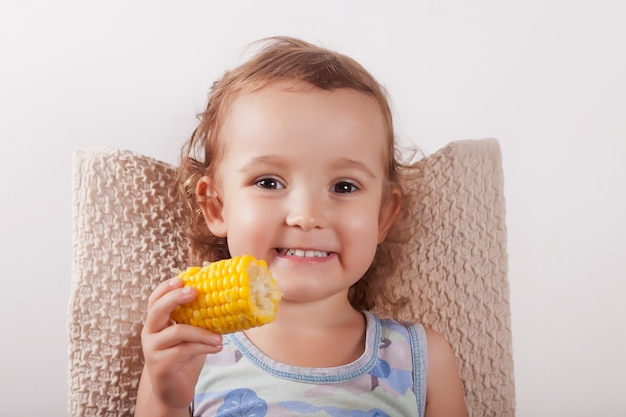 椅子に座ってトウモロコシを食べる巻き毛のかわいい女の子。