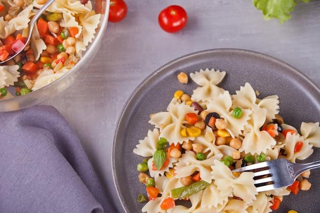 灰色の背景に灰色の皿にミックス野菜のファルファッレイタリアパスタ。
