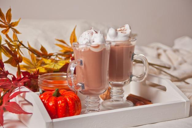 Два стакана горячего сливочного какао с пенкой на белом подносе с осенними листьями и тыквами на заднем плане